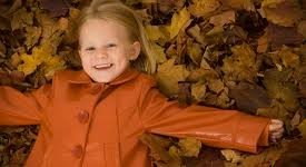 Little girl in fall coat and leaves